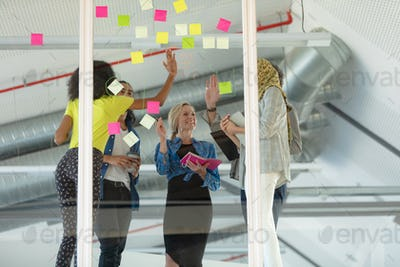 Diverse business people giving high five while discussing over sticky notes on glass wall