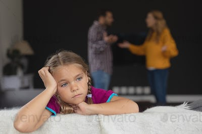 Sad girl leaning on sofa while Caucasian parents arguing in background