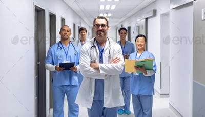 Diverse medical team of doctors looking at camera in corridor at hospital.