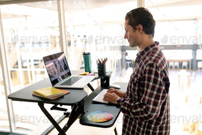 Side view of Caucasian male graphic designer working on laptop at desk in office