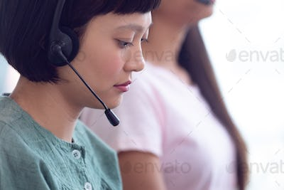 Side view of young Asian female customer service executive working on computer in office