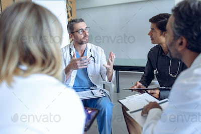 Diverse medical team discussing with each other in a circle in hospital.