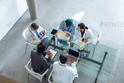 Diverse medical team discussing x-ray report over digital tablet at table in hospital.