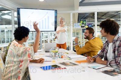 African american businessman raising hand in presentation during meeting
