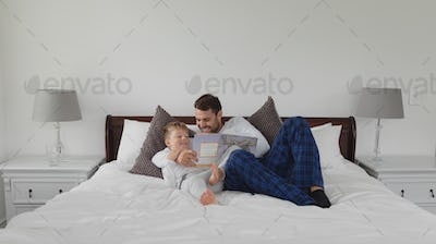 Caucasian father and son reading a story book while lying on bed in bedroom