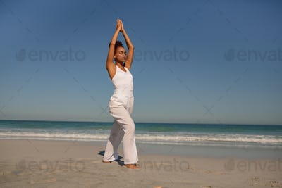 Front view of beautiful African american woman doing yoga at beach in the sunshine