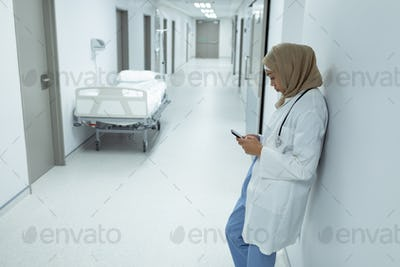Side view of mixed race female doctor in hijab using mobile phone at corridor in hospital