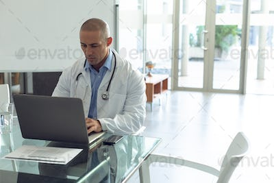 Front view of Mixed-race male doctor using laptop at table in the hospital