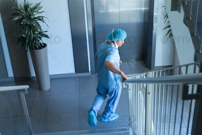 Side view of Caucasian male surgeon walking downstairs in hospital