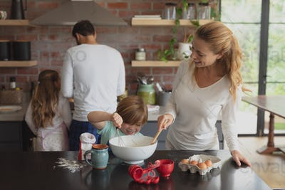 Happy Caucasian mother and son preparing cookie on worktop in kitchen