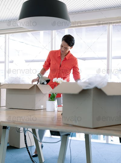 Caucasian businesswoman unpacking office belongings from cardboard boxes on table