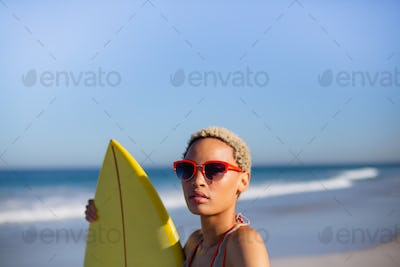 Front view of beautiful African american woman standing with surfboard at beach in the sunshine