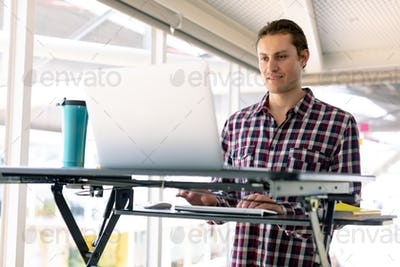 Front view of Caucasian male graphic designer working on laptop at desk in office