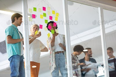 Business people discussing over sticky notes while diverse business people discussing over paper