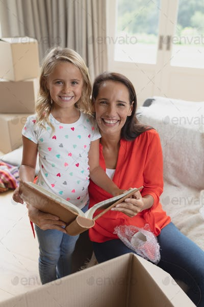 Front view of Caucasian mother and daughter looking at photo album in living room at home