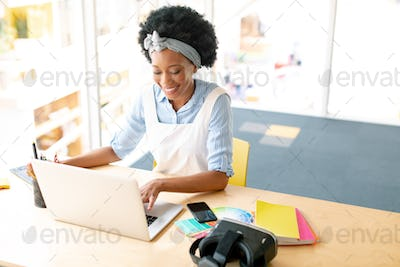 African american female graphic designer using graphic tablet and laptop at desk