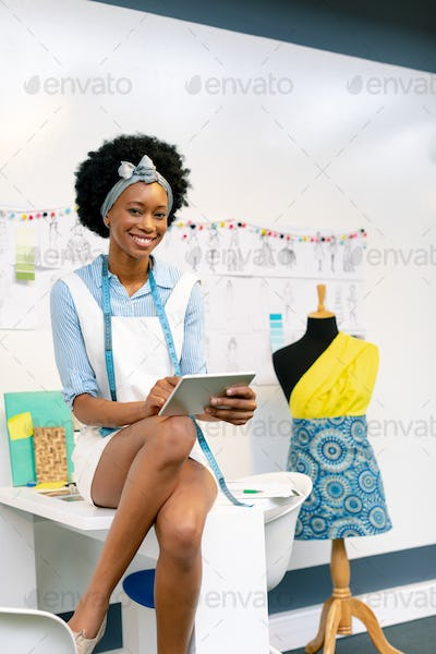 Front view of happy African american female fashion designer using digital tablet on table in office