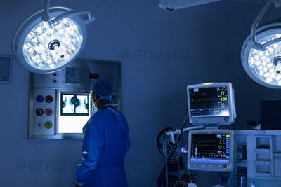 Rear view of Caucasian male surgeon reading x ray in operating room at hospital