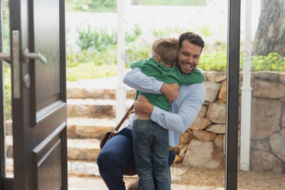 Front view of happy Caucasian father embracing his son as he enters the house