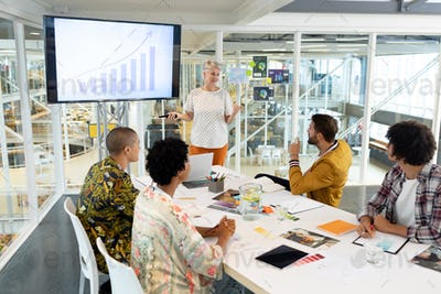 Mature Caucasian businesswoman giving presentation on screen during meeting