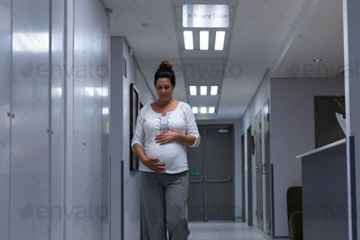 Front view of Caucasian pregnant woman touching her belly while walking in the corridor at hospital