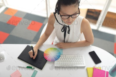 High angle view of female graphic designer using graphic tablet at desk in a modern office