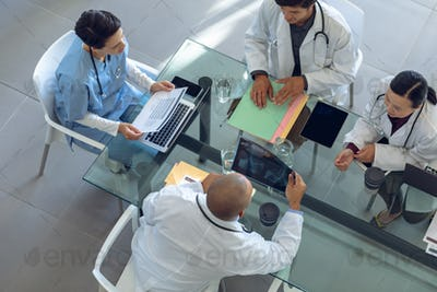 Diverse medical team discussing with each other at the table