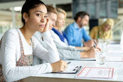 Thoughtful Mixed-race businesswoman looking away during a business meeting