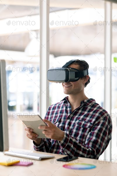 Caucasian graphic designer using virtual reality headset while working on digital tablet at desk