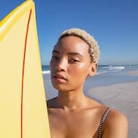 Beautiful African american woman in bikini standing with surfboard on beach
