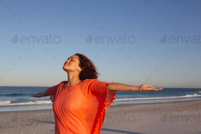 Side view of beautiful mixed race woman with arms stretched out standing on beach in the sunshine