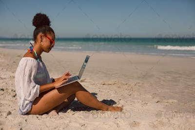 Side view of African american woman sitting on sand and using laptop at beach in the sunshine