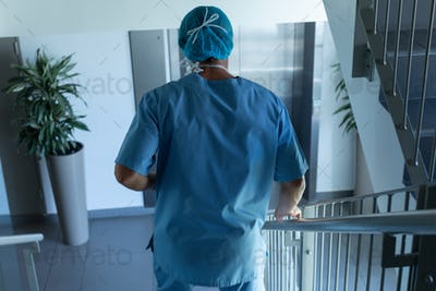 Rear view of Caucasian male surgeon walking downstairs in hospital