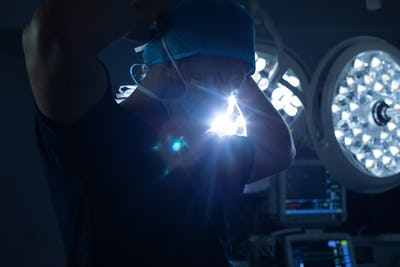 Caucasian male surgeon wearing surgical mask in operation theater with surgical equipment