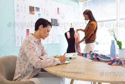 Attentive mixed race female fashion designers working in a modern office