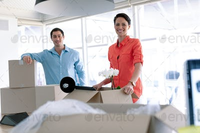 Business people looking at camera while unpacking office belongings from cardboard boxes on table