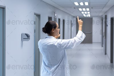 Mixed-race female doctor pretending to touch an invisible screen in the corridor