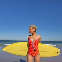 Beautiful African american woman in swimwear standing with surfboard on beach
