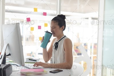 Asian female graphic designer drinking hot beverage while working on computer at desk