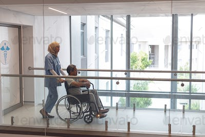 Mixed-race female doctor in hijab pushing senior mixed-race male patient in wheelchair at corridor