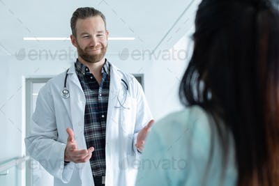 Front view of Caucasian male doctor interacting with pregnant woman in the corridor at hospital