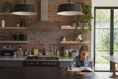 Front view of adorable Caucasian boy studying at table in kitchen at home