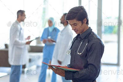 Caucasian male doctor looking at medical file. In the background diverse colleagues are discussing