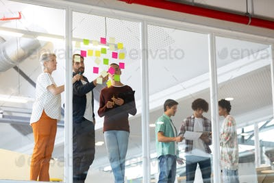 Business people discussing over sticky notes while diverse business people discussing over documents