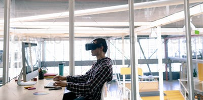 Caucasian male graphic designer using virtual reality headset while working on computer at desk