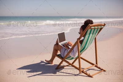 Side view of African american woman sitting on beach chair and using laptop at beach in the sunshine