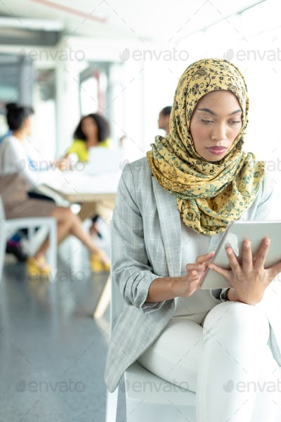 Beautiful Mixed-race businesswoman in hijab working on digital tablet
