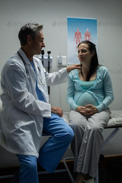 Caucasian male doctor examining a pregnant Caucasian woman on table