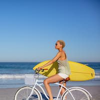 Side view of African american woman with surfboard sitting on bicycle at beach in the sunshine