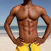 Mid section of shirtless African-american man with hands on hip standing on beach in the sunshine